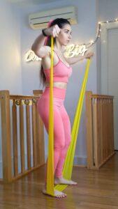 Mujer usando bandas elasticas guia de entrenamiento en casa